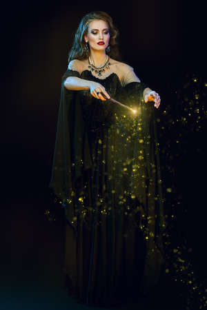 Full length portrait of a enchanting young witch in a hat and with a magic wand conjuring surrounded by magic lights. Halloween celebration, party.