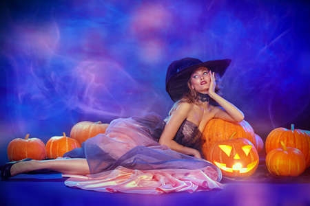 Charming beautiful witch lies with pumpkins lantern in a luxury evening dress and a hat. Halloween celebration, party. Copy space. Halloween fashion.