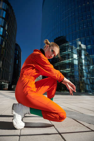 Fashion shot. Attractive young woman with bright makeup and in stylish colorful clothes posing on a big city street.