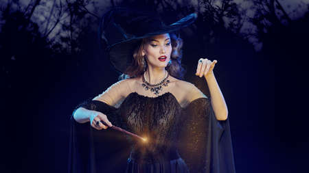 Portrait of a enchanting young witch in a hat and with a magic wand conjuring surrounded by magic lights against the background of the night forest. Halloween celebration, party.