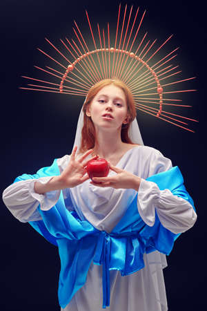 Modern art in religion. The Virgin Mary hold an apple on a dark background with rays of light.