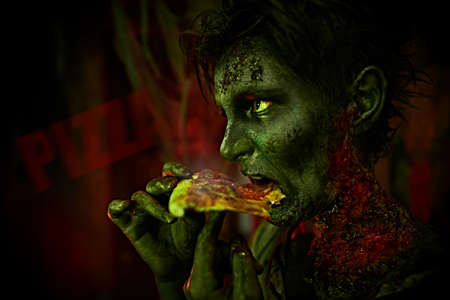 Cool and scary Halloween zombie boy teenager eating pizza. Halloween party.