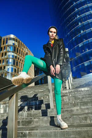 Cool modern girl in colorful clothes poses in a big city against the backdrop of skyscrapers. Fashion shot. 免版税图像