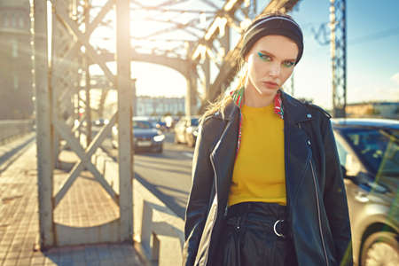 Trendy girl with bright makeup poses in stylish colorful clothes on a bridge in a big city. Fashionable urban style. 写真素材