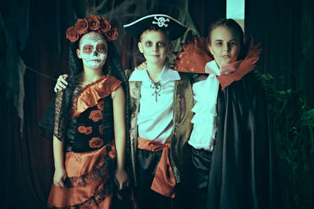 Three young friends celebrate Halloween on a party with old castle decorations. Halloween.