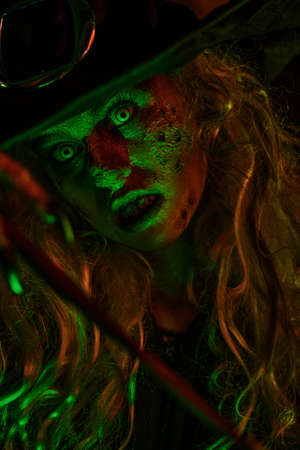 Close up portrait of scary ugly witch in green and red light. Halloween. Scary tales. Stockfoto