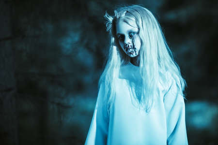 Portrait of a scary pale girl from a horror film in the forest. Zombie, halloween. Banco de Imagens