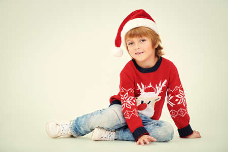 Christmas and New Year concept. Cute little boy in Santa Claus hat smiling at camera. Studio portrait over white background.