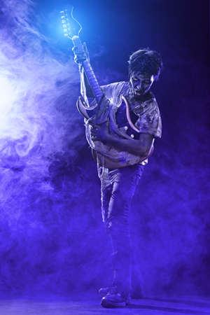 Halloween party. Scary zombie boy teenager plays electric guitar in the smoke. Standard-Bild