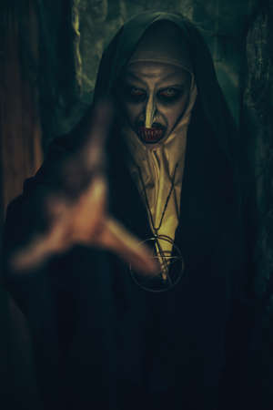 Halloween. Portrait of a cursed nun holding out her hand out of the dark. Horrors.