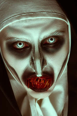 Close-up portrait of a devilish scary nun with bloody teeth looking at camera. Halloween and Horrors.