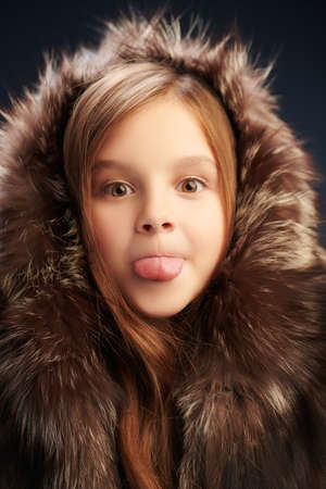 Portrait of a funny little in fur coat showing her tongue Child's play.