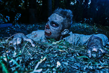 Zombie climbs out of the grave in the night cemetery. Halloween Horror. 写真素材