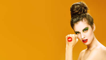 Portrait of an attractive girl with colorful makeup on a yellow background. Makeup and cosmetics. Studio shot. Standard-Bild