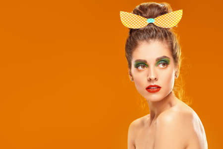 Beauty and pin-up style. Portrait of an pretty woman posing in paper bow in pin-up style on a orange background. Makeup and cosmetics. Studio shot.