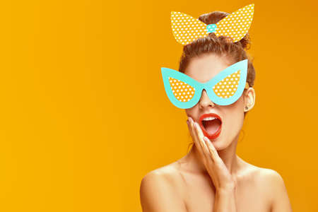 Portrait of an attractive playful girl with colorful makeup posing in paper sunglasses and a bow in pin-up style on a yellow background. Makeup and cosmetics. Studio shot.