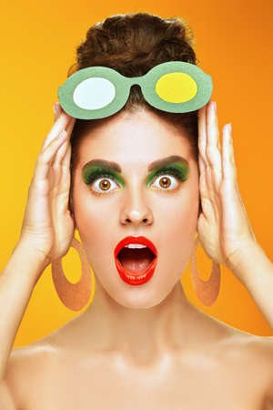 Beauty concept. Attractive young woman with colorful makeup posing posing in paper sunglasses and earrings on a vivid yellow background. Makeup and cosmetics. Studio shot.