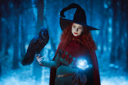 Halloween. Pretty young girl witch with a black raven and magic ball in a deep forest. Fairy tales.