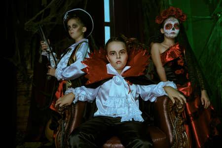 Children celebrate Halloween are posing on a party with old castle decorations. Halloween.