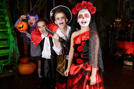 Halloween. Funny scared kids in carnival costumes wander through the old castle on Halloween.