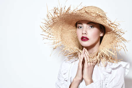 Portrait of a beautiful romantic girl in a white blouse and straw hat. Summer season. Beauty and cosmetics.
