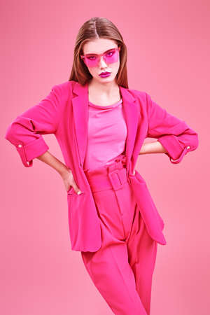 Beautiful fashion model posing at studio in trendy crimson suit and sunglasses on a pink background. Glamorous pink style. Imagens