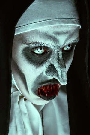 Close-up portrait of a devilish scary nun with bloody teeth. Halloween and Horrors. Standard-Bild