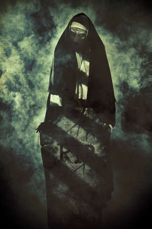 Halloween and Horrors. Devilish evil nun in a cemetery with a tombstone. Mysterious fog around.
