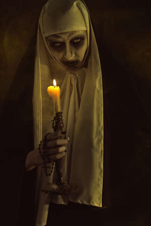 Scary devilish possessed nun standing with a candle in a dark room. Horrors and Halloween.