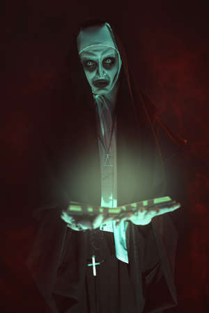 An evil cursed nun with a bible and a cross in her hands looks at the camera on a black background with a blood-red haze. Halloween. Horrors. Copy space.