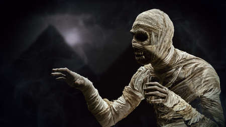 Scary evil mummy against the background of the Egyptian pyramids in night. Halloween. Ancient Egyptian mythology. Stock Photo