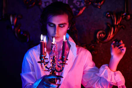 A vampire aristocrat walks with candles in the night castle. 19th century style. Halloween.