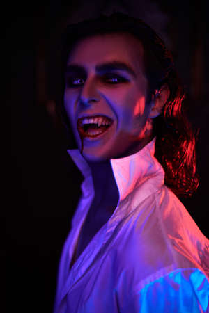 Portrait of a scary bloodthirsty vampire in red light. Halloween.