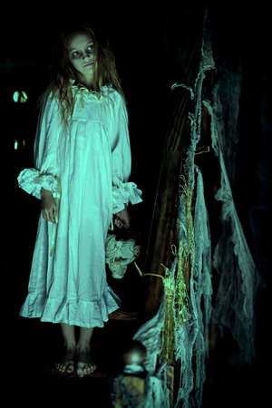 Scary little girl ghost in a white nightgown standing barefoot on the stairs and holds her doll and. Black background. Halloween. Stock fotó