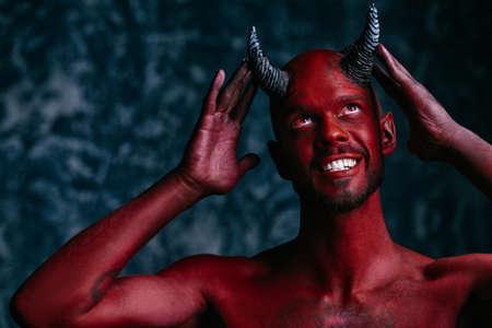 A portrait of a joyful demon over the grunge background. Horror movie, nightmare. Halloween.