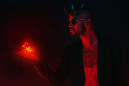 A portrait of a bad demon in sunglasses with fire in hand. Horror movie, nightmare. Halloween.