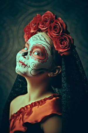 Side view portrait of a child girl in a costume of Calavera Catrina over dark background. Little girl with sugar skull makeup. Halloween. Dia de los muertos. Day of The Dead.