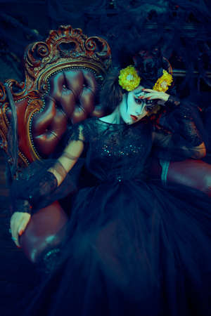 Sugar skull girl. Day of The Dead. Dia de los muertos. Charming and dangerous Calavera Catrina sitting on armchair. Halloween.