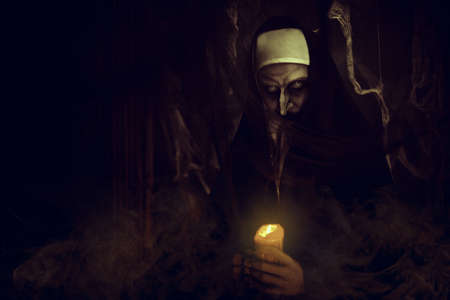 Frightening devilish possessed nun standing with a candle in a dark room. Horrors and Halloween. Standard-Bild