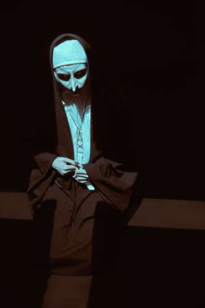 Scary devilish nun prays standing in a dark room in light in the form of a cross. Horrors and Halloween. Standard-Bild