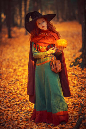 Halloween. Charming young girl witch with long red hair stands in a deep forest with a pumpkin. Fairy tales. Copy space.