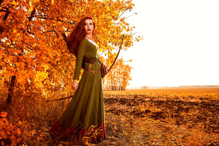 Historical reconstruction. Beautiful young woman archer with magnificent long red hair in a historical celtic dress stands on the edge of the forest. 版權商用圖片