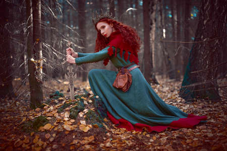 A beautiful queen warrior woman with a sword in a deep forest. Ancient legends. Fantasy world. 版權商用圖片