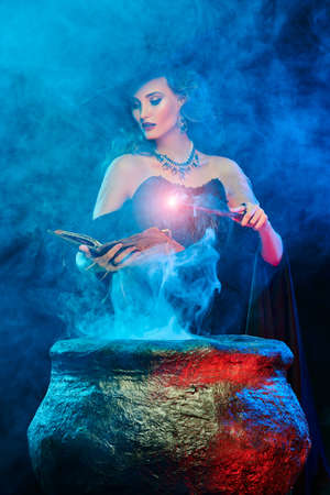 Halloween magic. A beautiful young witch in a hat and with a magic wand conjures over a cauldron surrounded by magical fires.