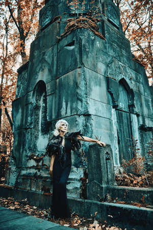 An aristocratic old widow woman with beautiful gray hair and a rich black dress stands sad next to a crypt in a cemetery. Black Widow. Atmosphere of mysticism. Halloween.