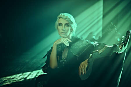 A beautiful old woman, a noble widow with gray hair and a rich black dress, sits on a vintage sofa in her old castle in the rays of light. Black widow. Fantasy world. Halloween. Banco de Imagens