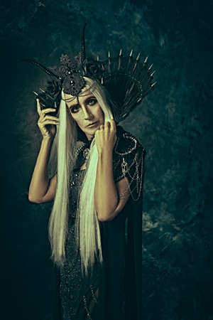 A portrait of a stately and beautiful old woman with long gray hair, in a rich headdress and a rich black dress against a dark grunge background. Black Queen, Witch. Halloween.