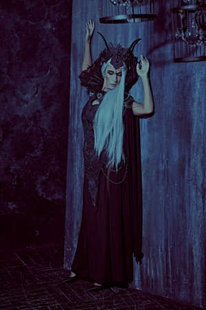 A portrait of a stately and beautiful old woman with long gray hair, in a rich headdress and a rich black dress in a dark castle. Black Queen, Witch. Halloween.