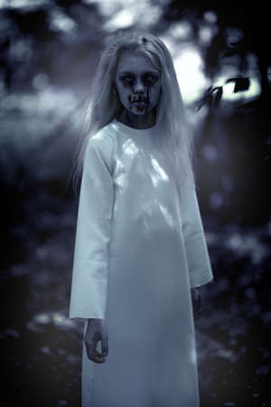 A portrait of a scary pale girl in the forest. Zombie, halloween. Banco de Imagens