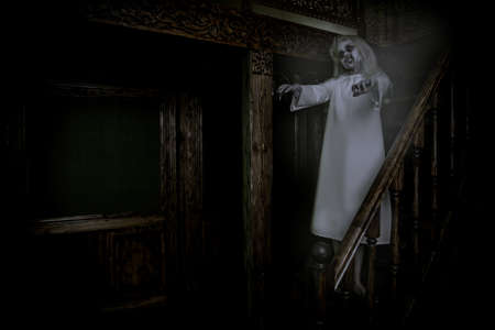 A full length portrait of a scary pale girl from a horror film in a room on the stairs. Zombie, halloween.